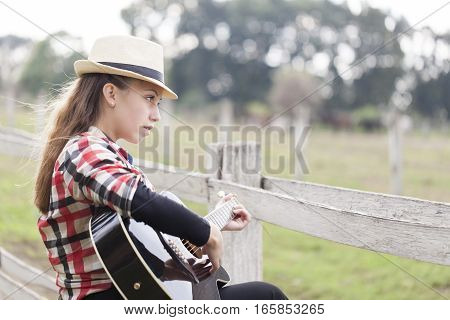Beautiful young girl with a guitar in the nature Selective focus and small depth of field lens flare