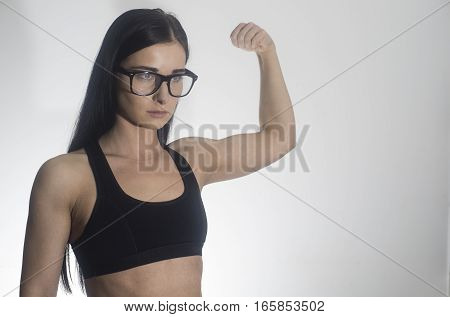 Beautiful girl. The girl shows biceps. Slim fitness woman on a white background. Girl in glasses. Beautiful girl in sportswear. Space for text