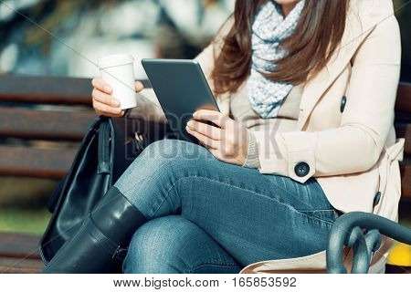 Young woman in the street drinking morning coffee and use her digital tablet.
