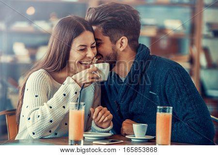 Happy beautiful couple having fun in cafe.
