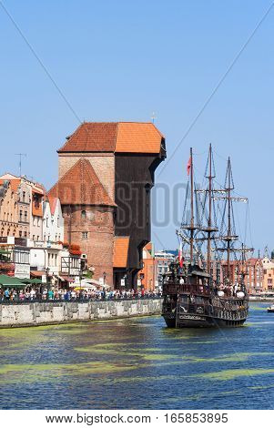 GDANSK POLAND - AUGUST 27 2016: Old city with medieval wooden port crane the oldest in Europe Motlava river tourist pirate ship and crowd of people walking along the quay