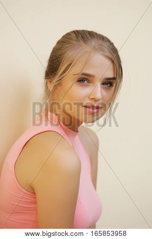 Pretty cute young woman or girl with blonde hair in pink shirt with sensitive face on beige background