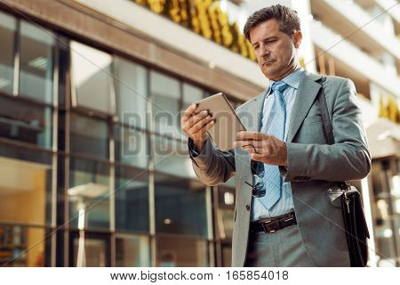 Close up portrait of a successful businessman while using a digital tablet.