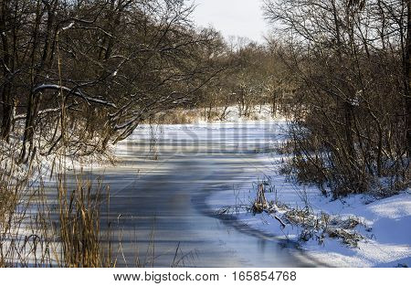 the winter landscape of small frozen river