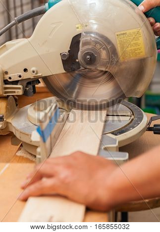 carpenter's hands on wood at table saw making a cut stock photo