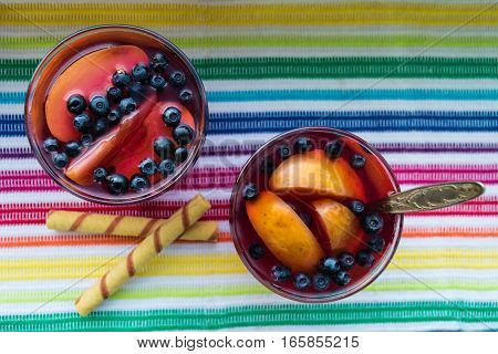 Homemade compote with apples and blueberry on the color towel