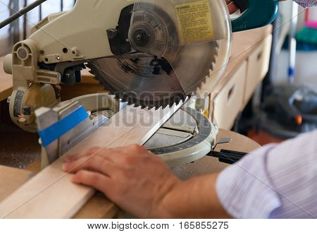 carpenter's hands on wood at table saw stock photo