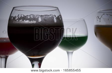 Glass beakers of different colors, green, red, yellow and black