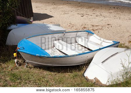 Aluminium dinghies tied up on the beach