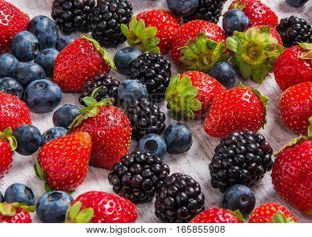strawberries blackberries blueberries arranged on the table