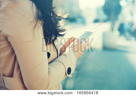 Young woman walking and using a smart phone on a city street.