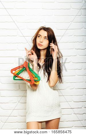 Woman With Hangers And Phone