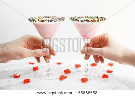Man and woman hands taking pink milk shake cocktail, close-up. Decorated with jelly hearts and sprinkles. Saint valentine's day.