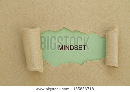 mindset word written under torn paper .