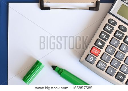 Crop shot of calculator, empty white sheet and a green pen, suggesting calculation of financial aspects, template for text