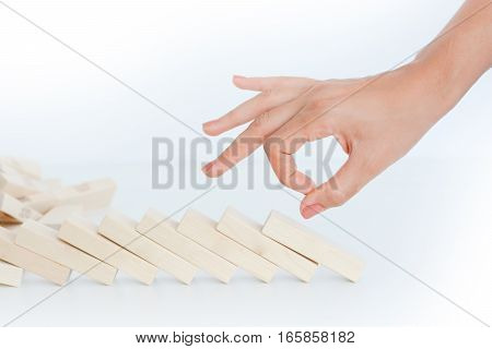 Human hand starting a domino effect concept with wooden blocks