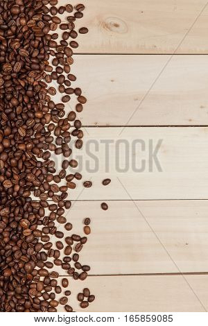 Frame with roasted coffee beans on wood background
