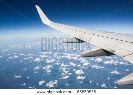 Photograph of an airplane wing over the blue sky