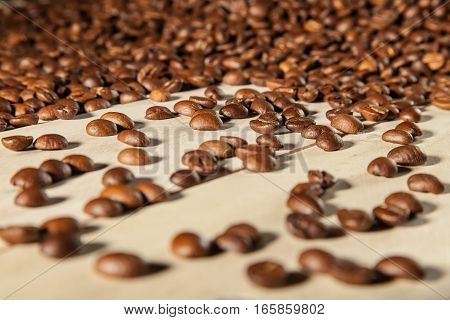 Roasted coffee beans on wooden background. Detailed close up