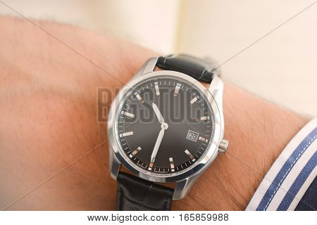 Close-up shot of a watch on a businessman wrist suggesting poor time management, being out of time or running late