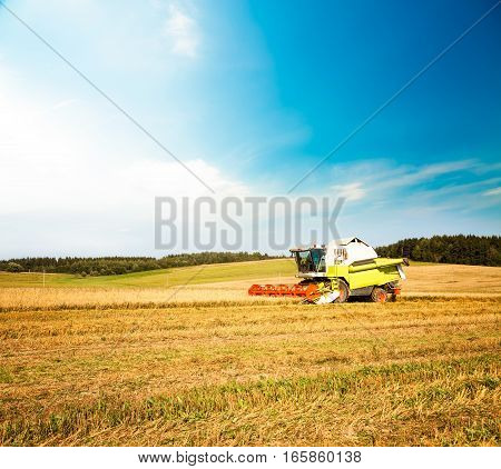 Working Harvesting Combine in the Oat Field. Farmland Background. Agriculture Machinery and Harvest Concept. Harvester Farm Machine. Toned Photo with Copy Space.