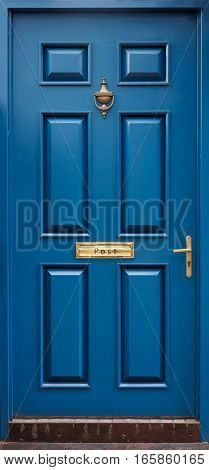 Classical blue door with golden postbox, knocker, knob