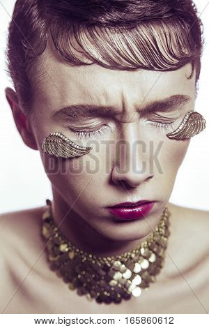 High fashion beauty of young model with gold wings piercing jewelry and makeup. studio shot.