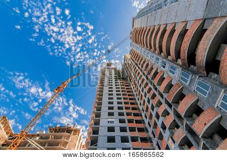 Construction crane working at construction of a multistory building on the blue sky background