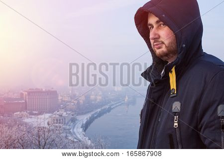 Portrait of a serious bearded man in hood against winter cityscape at sunset