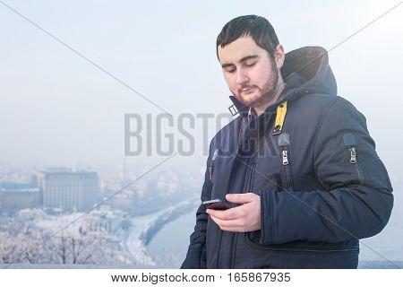 Man traveler using phone against winter cityscape