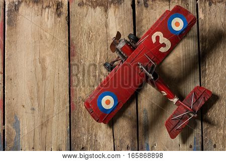 Vintage red toy bi plane on a worn wooden background