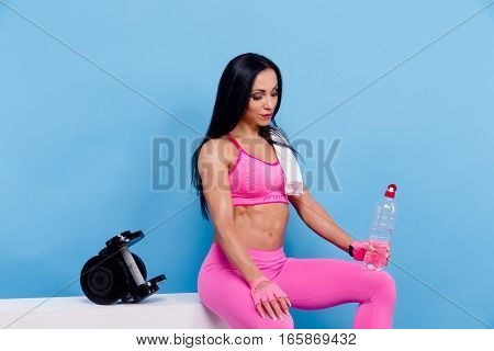 Muscular woman in pink leggings, top and gloves having a rest, sitting and hold plastic bottle of water