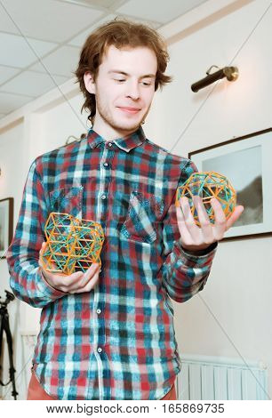 Young smiling man in a plaid shirt standing and holding coloured three-dimensional models of geometric solids.
