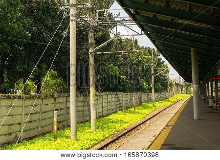 Commuter railway with green bushes view from a station photo taken in Depok Indonesia java