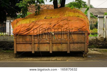 An orange tailgate of garbage truck fullfilled with trashes and covered by plastic photo taken in Jakarta Indonesia java