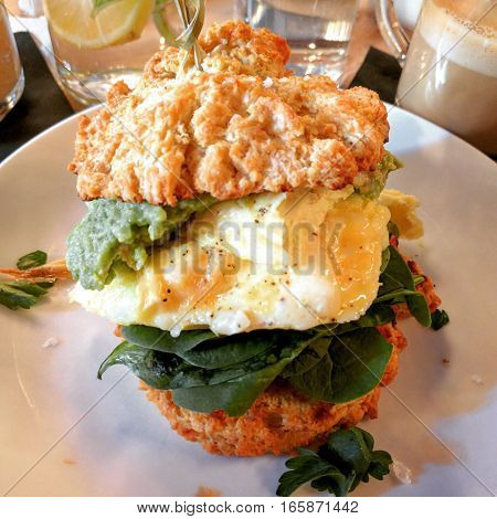 Scrambed eggs, avocado, baby spinach and tomato jam on buttermilk biscuits