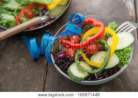 Fresh vegetables salad on wooden background .