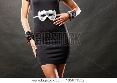 Holidays people and celebration concept. Woman black dress with silver carnival venetian mask on dark background part of body