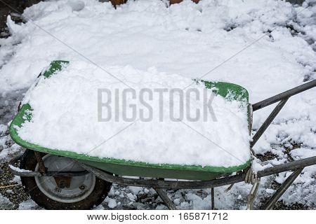Piled up snow on wheelbarrow for snow removal work