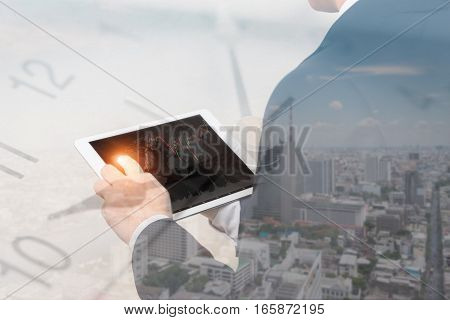 Double exposure of businessman using the tablet with cityscape and financial graph on blurred building background with time Business Trading concept