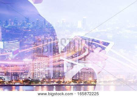 Double exposure businessman using tablet and cityscape night view Business technology concept