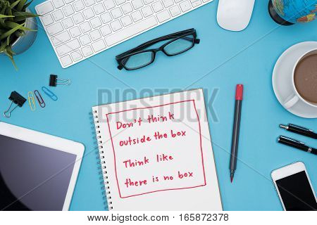 Think different business concept Do not think outside the box think like there is no box on notebook with office supplies over blue desk table background