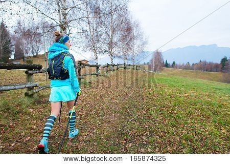 Sporty woman walking in nature in sports skirt