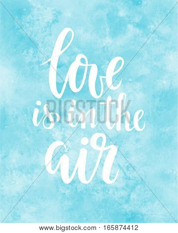 love is in the air Hand drawn creative calligraphy and brush pen lettering on blue watercolour background. design for holiday greeting card and invitation of the wedding Valentine's day and Happy love day