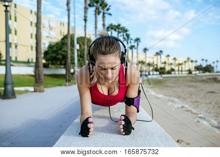 Young blonde woman exercising on beach a