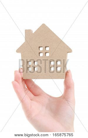Hand holding miniature model of house on white background