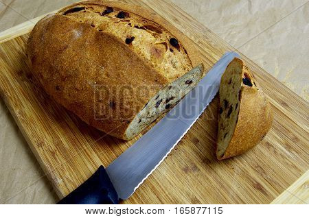 A loaf of homemade olive bread sits on a cutting board. The end has been cut off using the bread knife that also lies on the board.