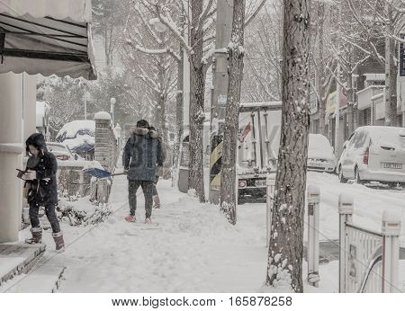 DAEJEON, SOUTH KOREA - JANUARY 20: Newly fallen snow turns city white. Man shovels snow while child seeks shelter to use her phone.
