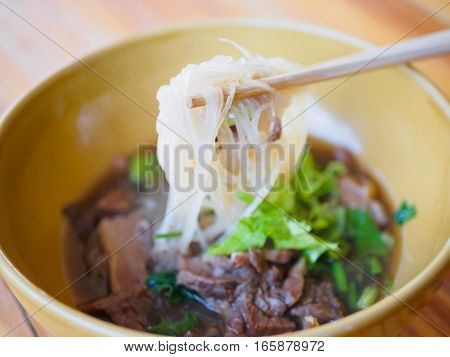 beef noodle with hot soup in a brown bowl with a Pair of Chopsticks put on wooden table. Asia food