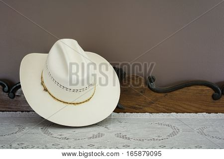 A White Cowboy Hat On An Antique Cabinet